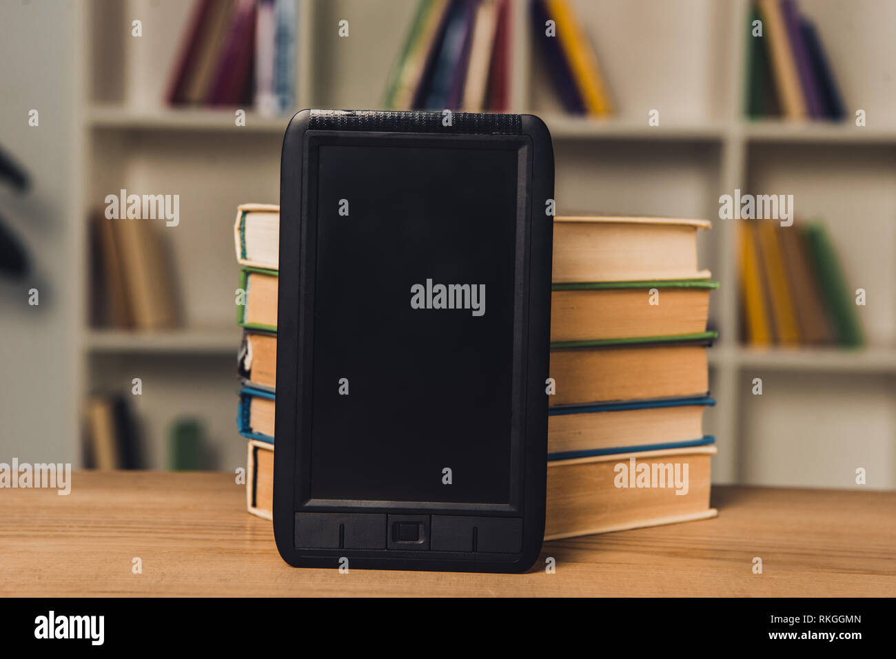 e-book with blank screen near paper books on table - Stock Image