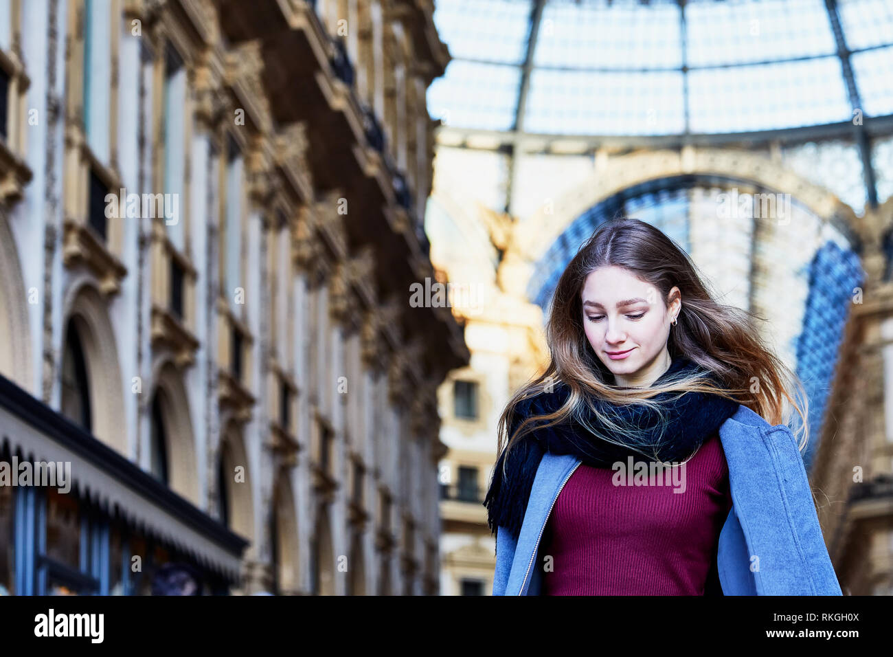 Girl daydreaming while walking inside of Galleria Vittorio Emanuele II in Milan Italy Stock Photo