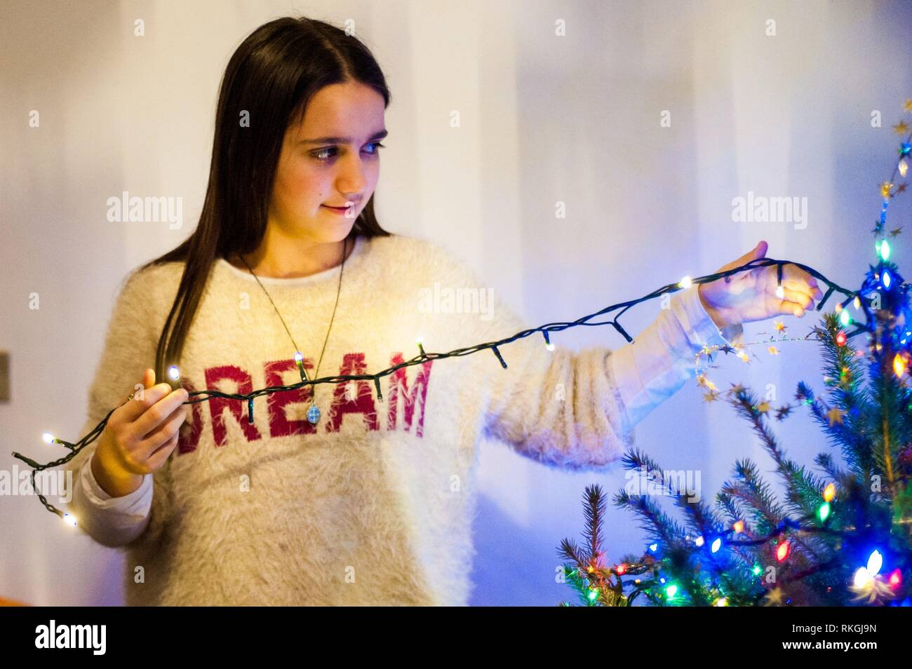 girl at home while decorating Christmas tree. - Stock Image