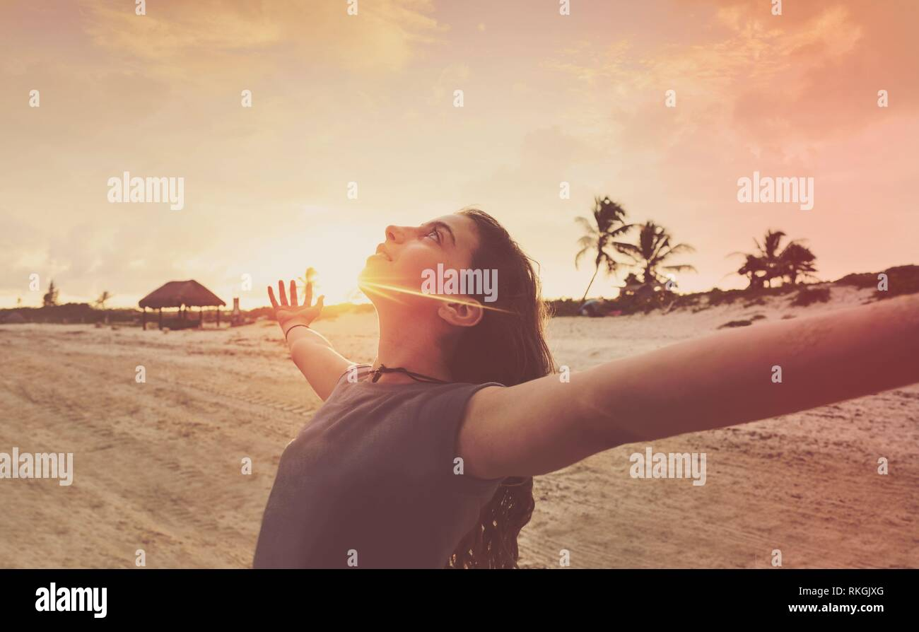 Open arms girl at sunset caribbean beach in Mexico. - Stock Image