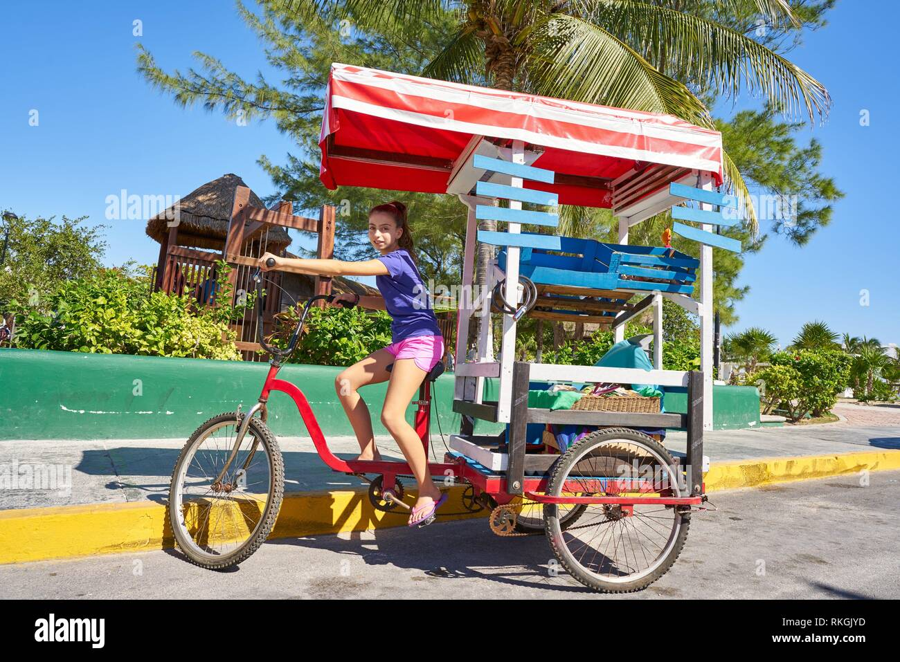 Young girl with caribbean bicycle shop on tricycle of Mexico. Stock Photo