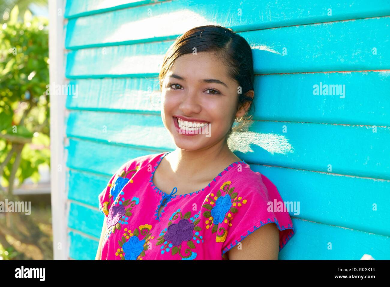 2a59d738e170 Mexican latin woman with mayan dress smiling in turquoise wall Stock ...