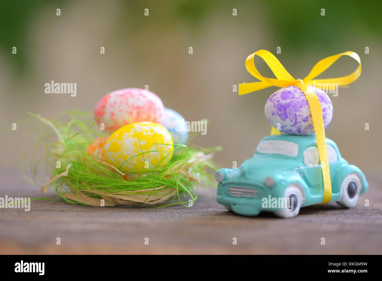 Toy car carrying easter egg in spring time. Stock Photo