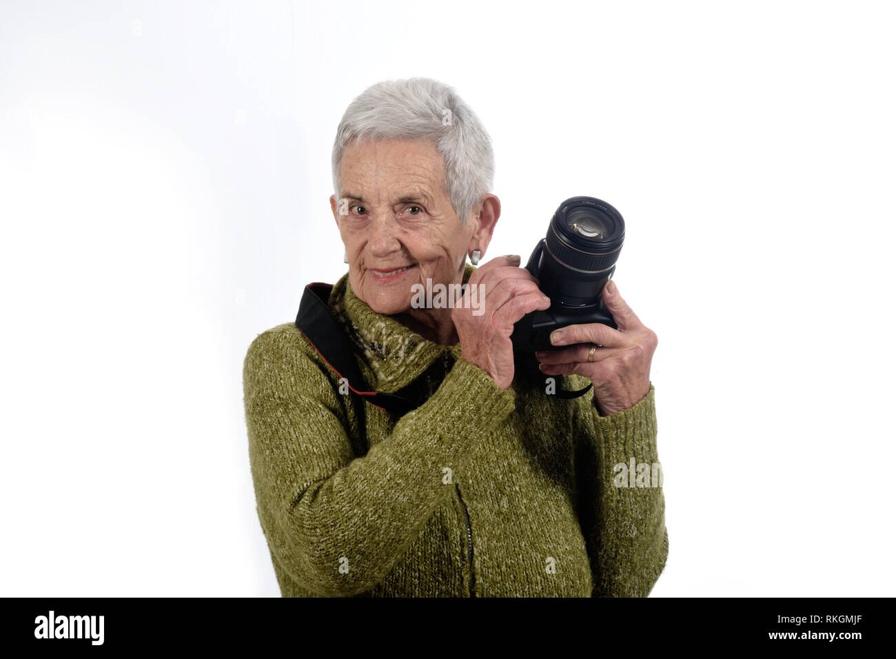 Portrait of a senior woman with SLR camera. - Stock Image