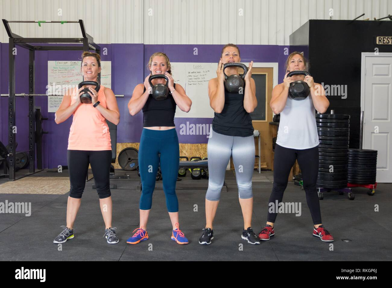 Four girls with kettle bells doing a workout together at a crossfit gym. - Stock Image
