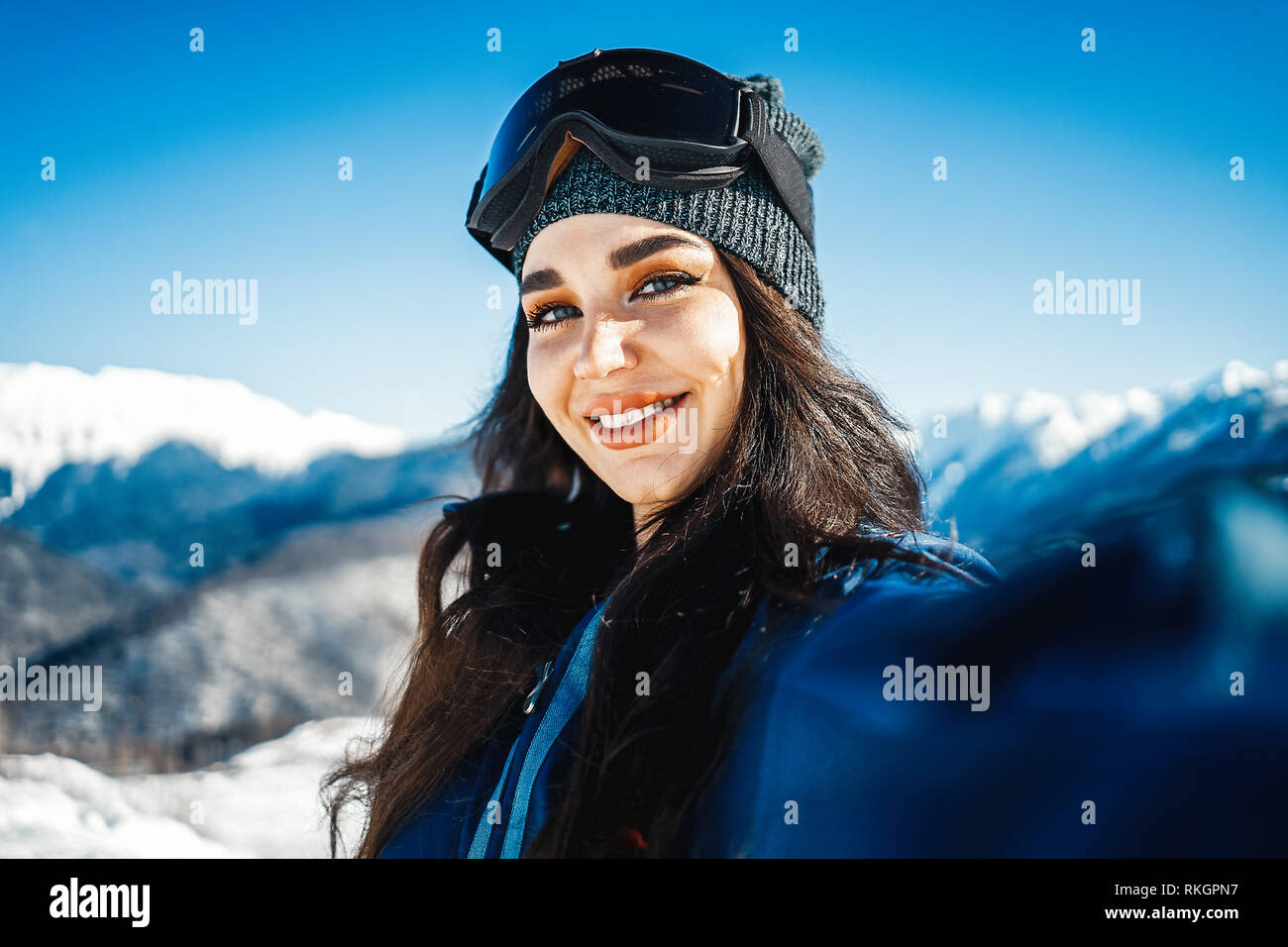 Attractive snowboard girl smiling and making selfie on mountain background.  - Stock Image 129774694
