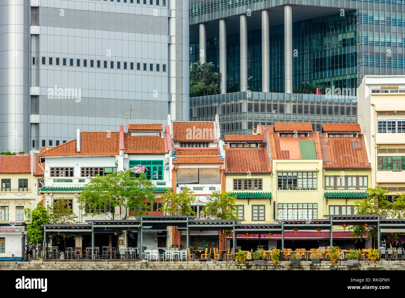 Tourist attraction Boat Quay at Raffles Place shophouse restaurants and bars with commercial office buildings during day time - Stock Image
