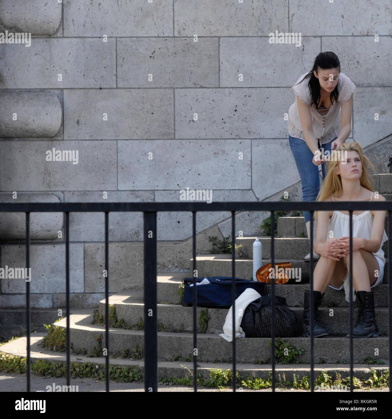 """PARIS MODE - FASHION MODEL HAVING A MAKE UP ON THE SPOT OF """" LES BERGES DE LA SEINE """" DURING A SHOOTING OUTSIDE ASSISTED BY A YOUNG HAIR DRESSER GIRL - PARIS WOOMAN - SCEANCE PHOTO D'UN MODEL SUR LES QUAIS - PHOTOGRAPHY MODEL IN PARIS - FRENCH ELEGANCE - COLOR ARCHIVE © Frédéric BEAUMONT Stock Photo"""