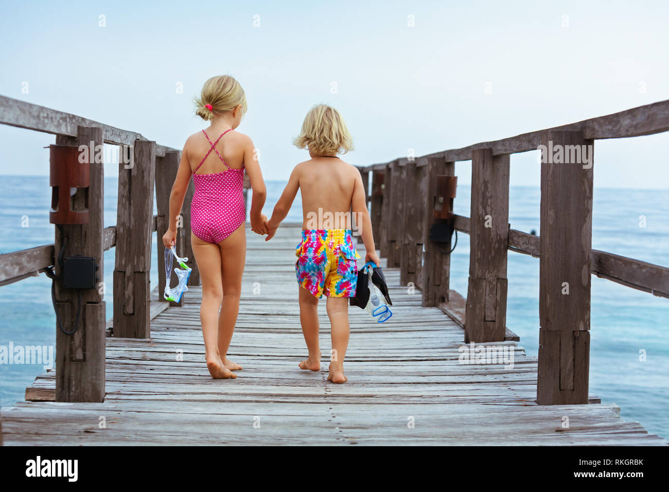 Happy children with snorkeling mask, fins going to dive in tropical sea to exploring underwater nature. Travel lifestyle, water sports, swimming adven - Stock Image