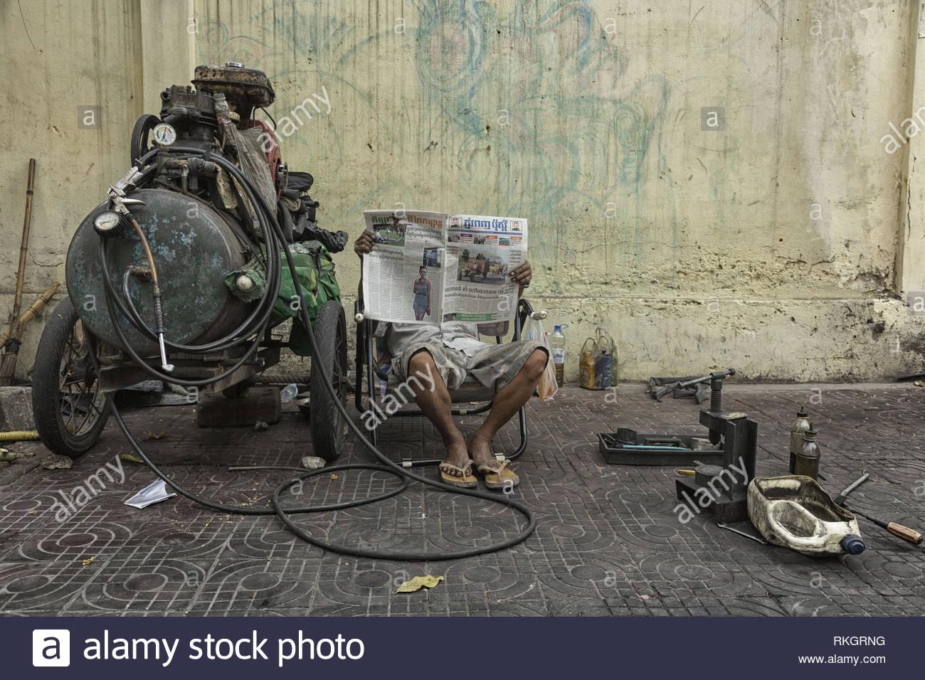 Flat tire repairmen reading newspaper in Phnom Penh Stock Photo