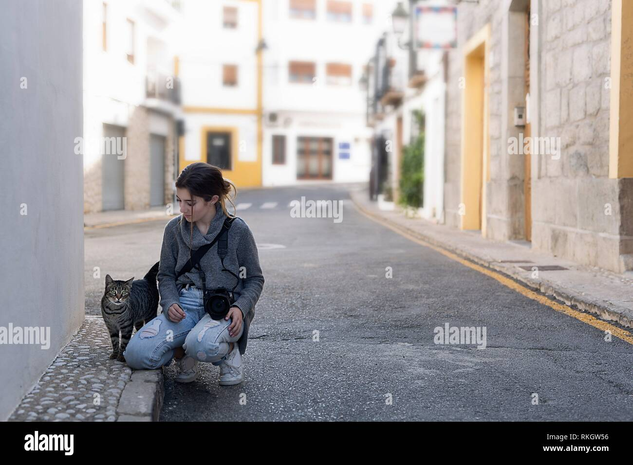 Teenage girl with her photo camera greeting a street cat in the town of Altea, in the province of Alicante, Spain. - Stock Image