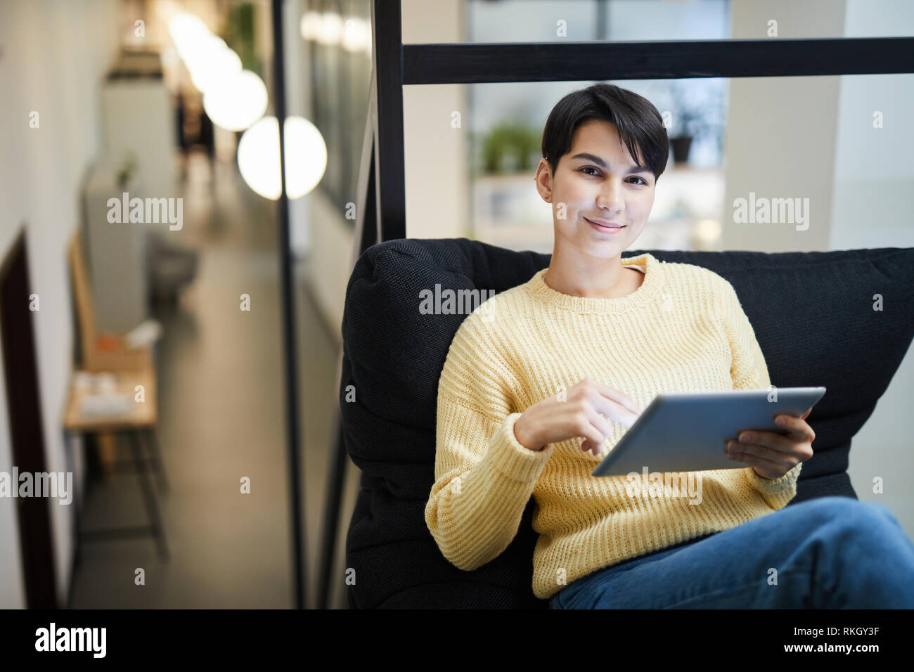 Pretty lady using tablet in cozy office - Stock Image