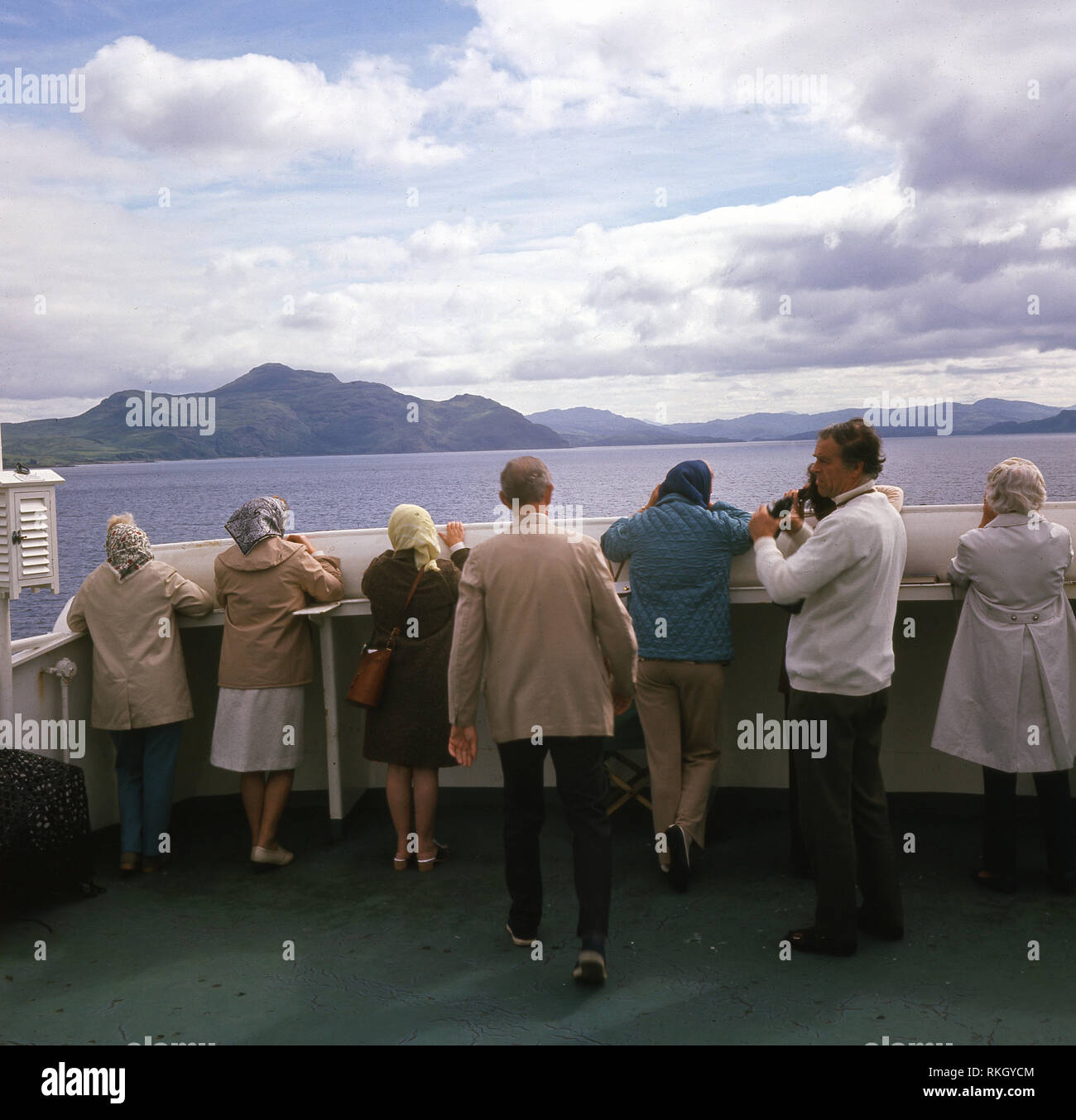 1960s, daytime and passengers on a ferry looking out at the Sound of Mull, a sound ( an ocean channel) between the Inner Hebridean Island of Mull and Scotland. The sound is part of of the Atlantic Ocean on the West Coast of Scotland, - Stock Image