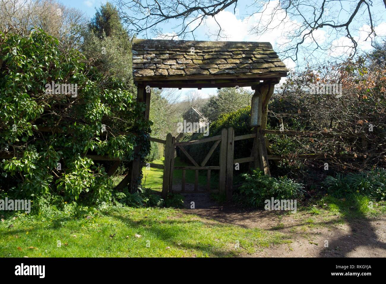 Spring sunshine on the picturesque lychgate to the tiny old Saxon church at Duntisbourne Rouse in the Cotswolds, Gloucestershire, UK. - Stock Image