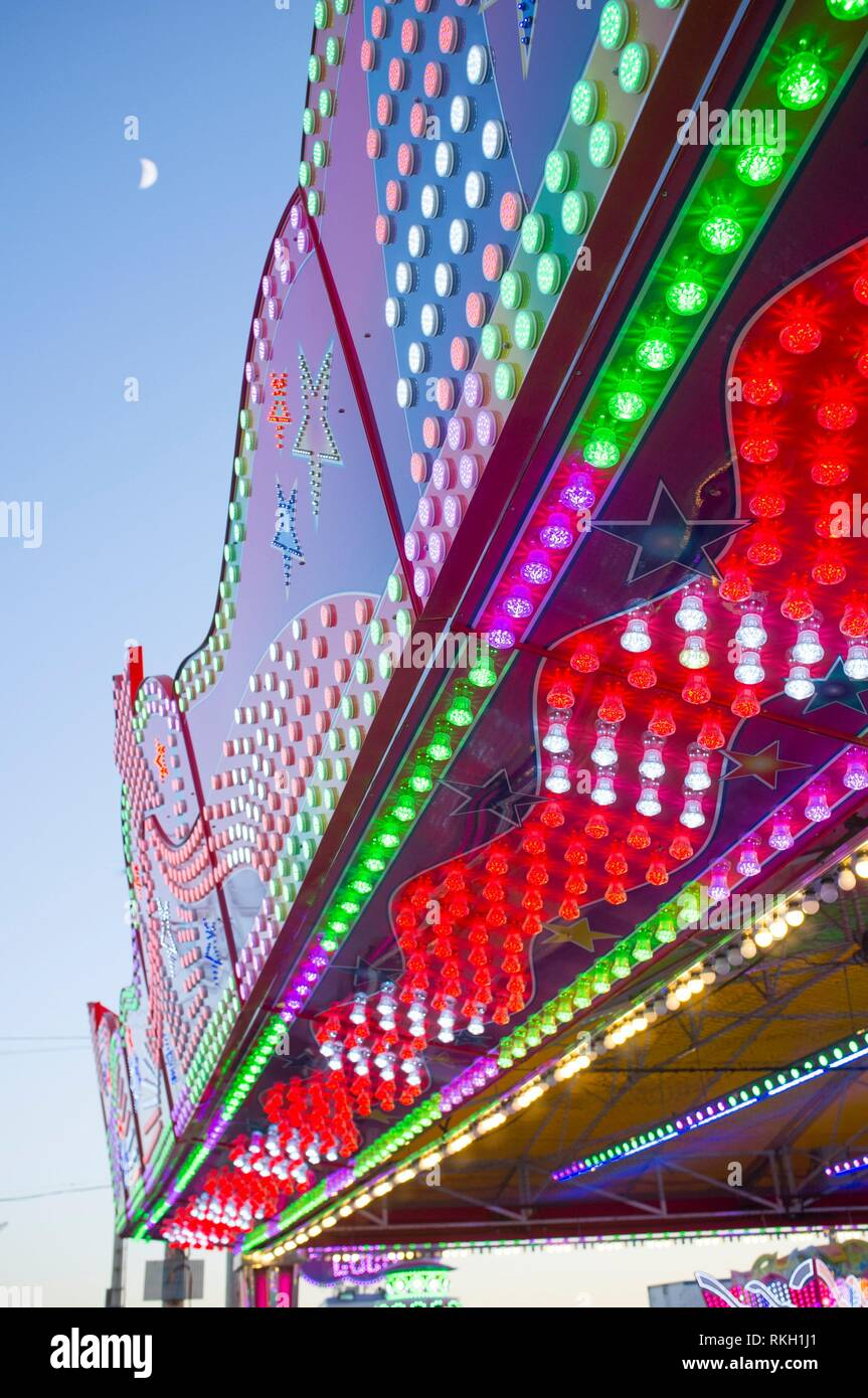 Fairground attraction front plenty of bulbs, leds, balloons and colors. Daylight shot. - Stock Image