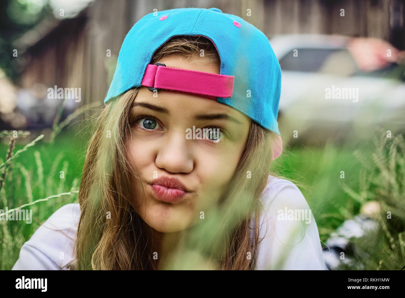 A teenager girl in a blue baseball cap is lying on the grass in the village and is grimacing or blowing a kiss. Serene outdoor recreation. Female port - Stock Image