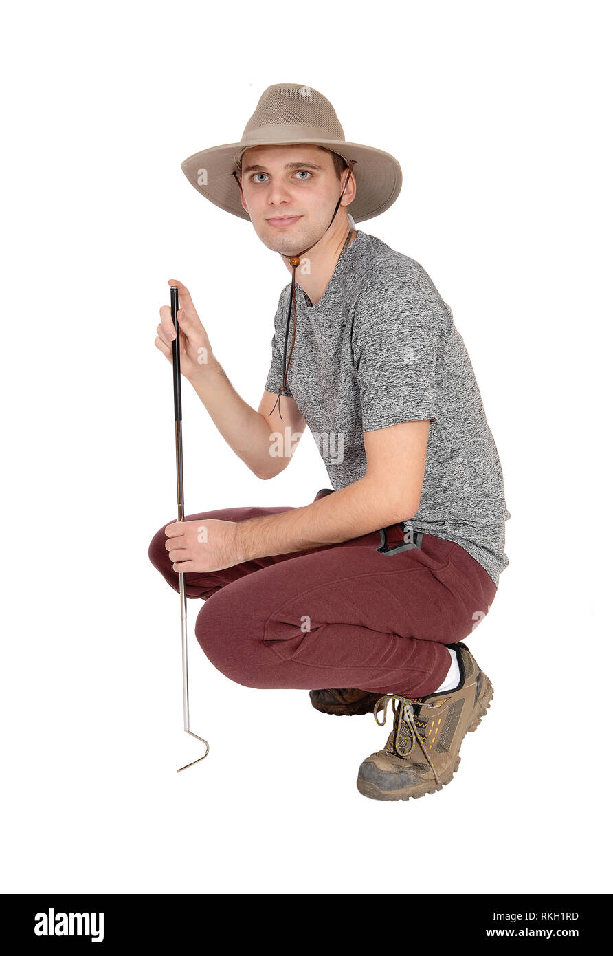 A slim young man in a gray sweater with a safari hat and a tool to catch some snags crouching on the floor, isolated for white background - Stock Image