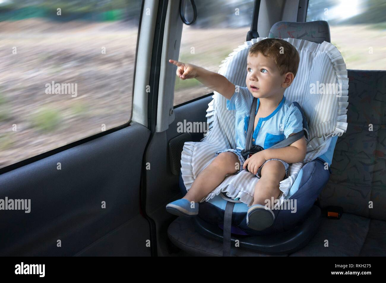 Cute little boy observing the countryside from his car safety seat. He is pointing something. - Stock Image