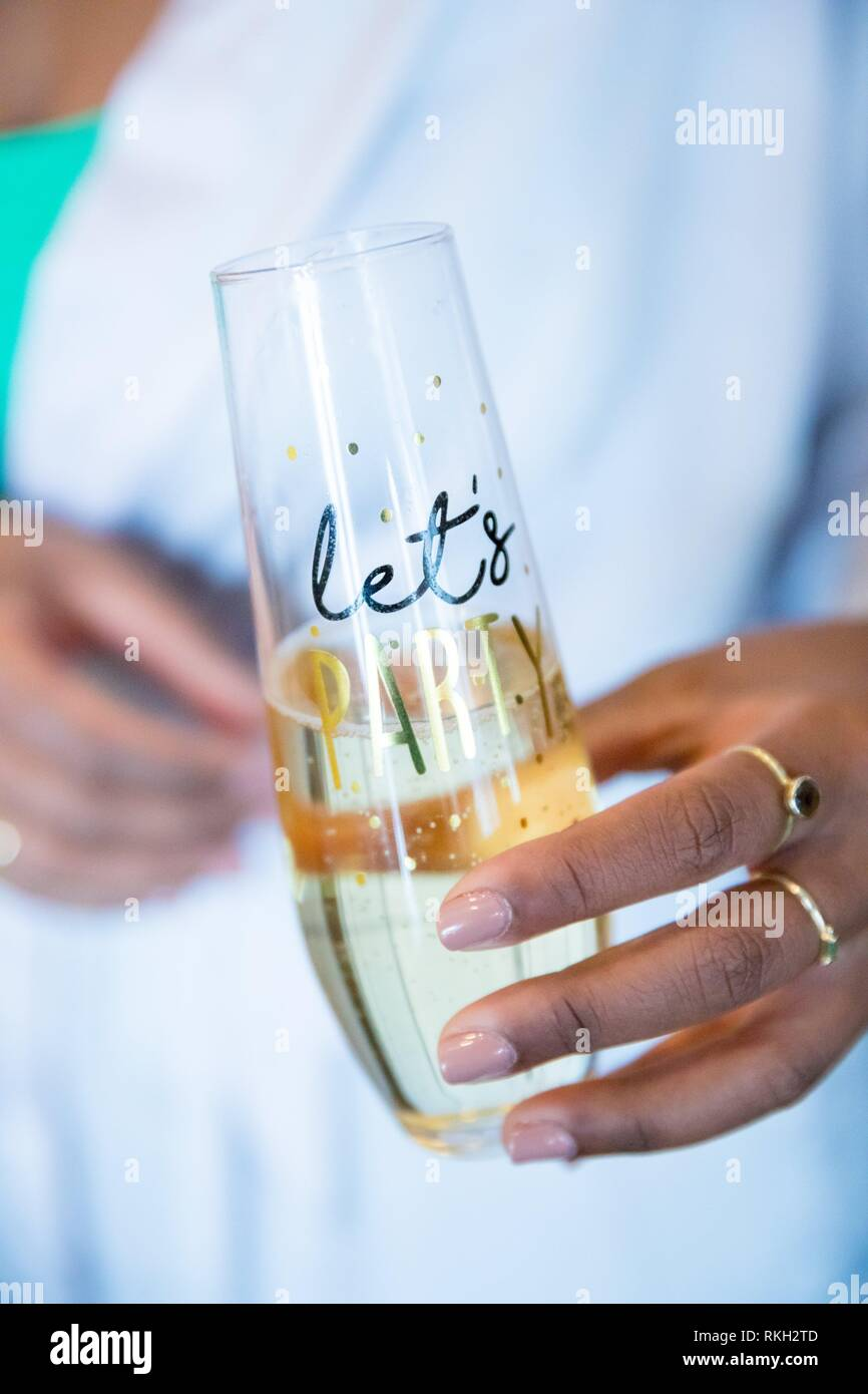 Champagne flute with let's party written on it during a wedding day in the bridal suite. - Stock Image