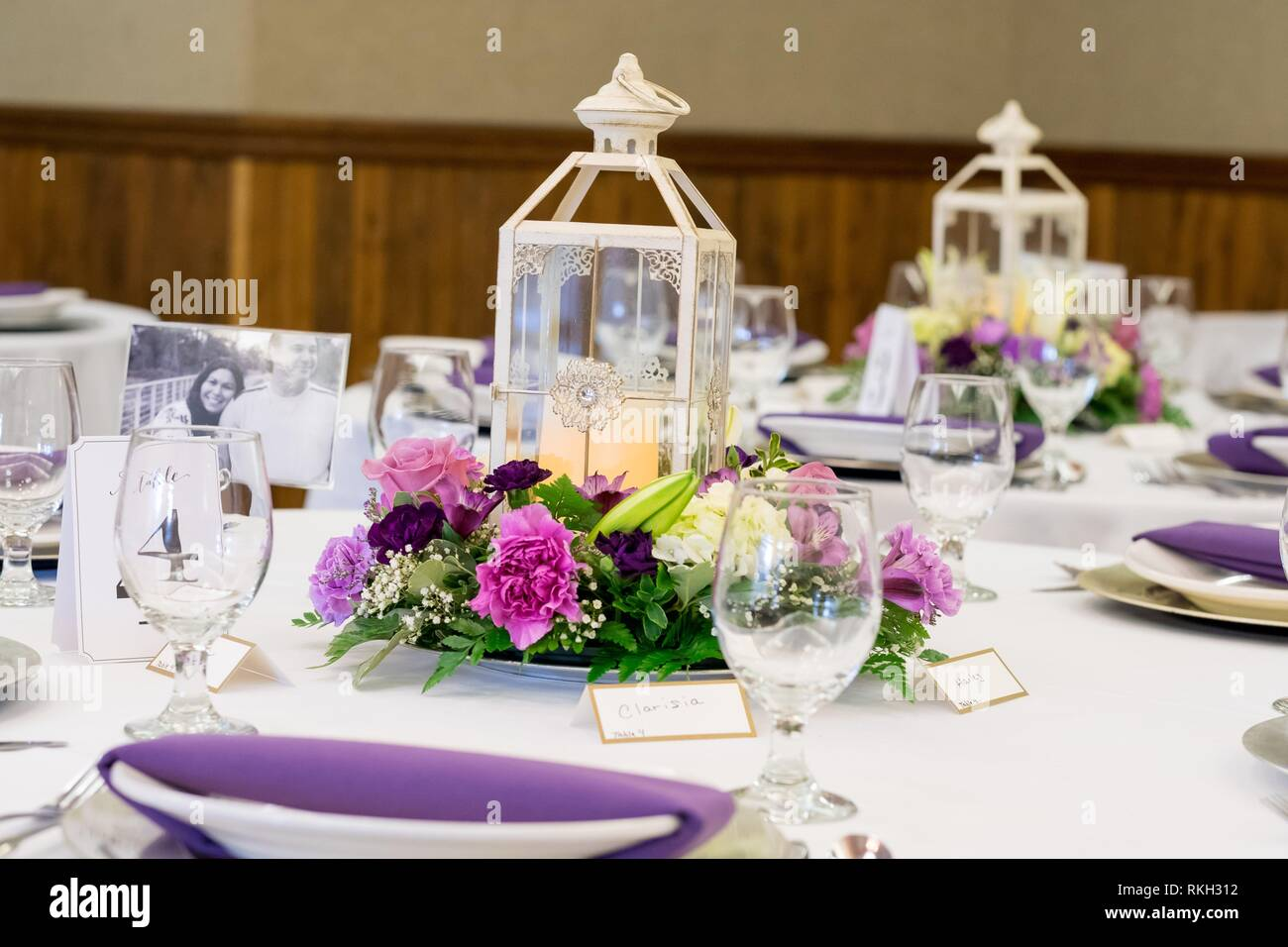 Wedding reception centerpieces of candle lanterns on tables decorated with  flowers from a local florist Stock Photo - Alamy