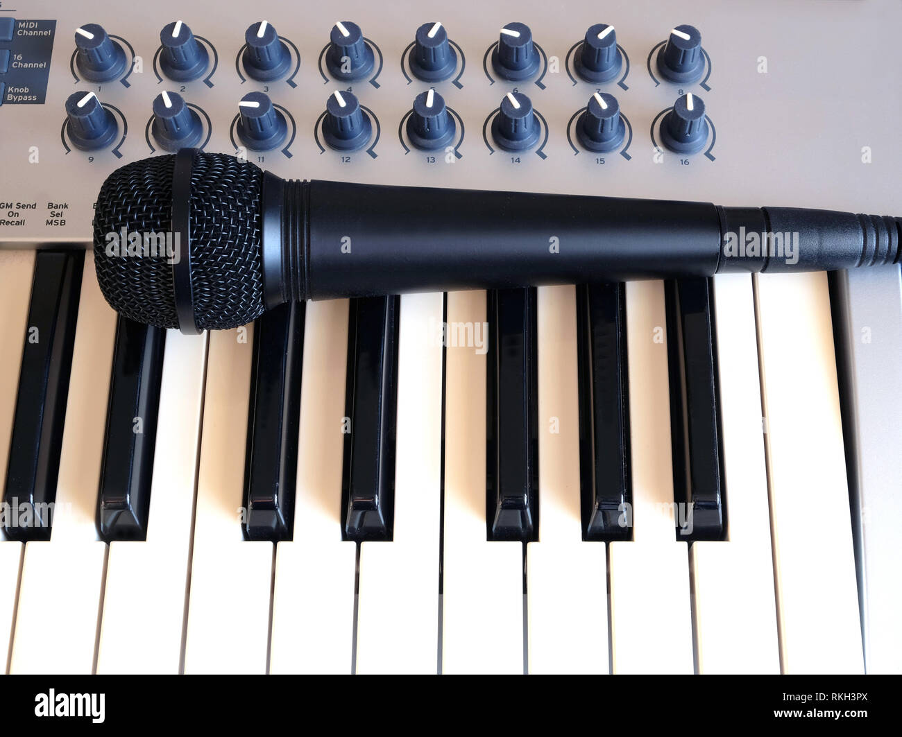 Black microphone on electronic synthesizer keyboard with many control knobs on denim background top view closeup - Stock Image