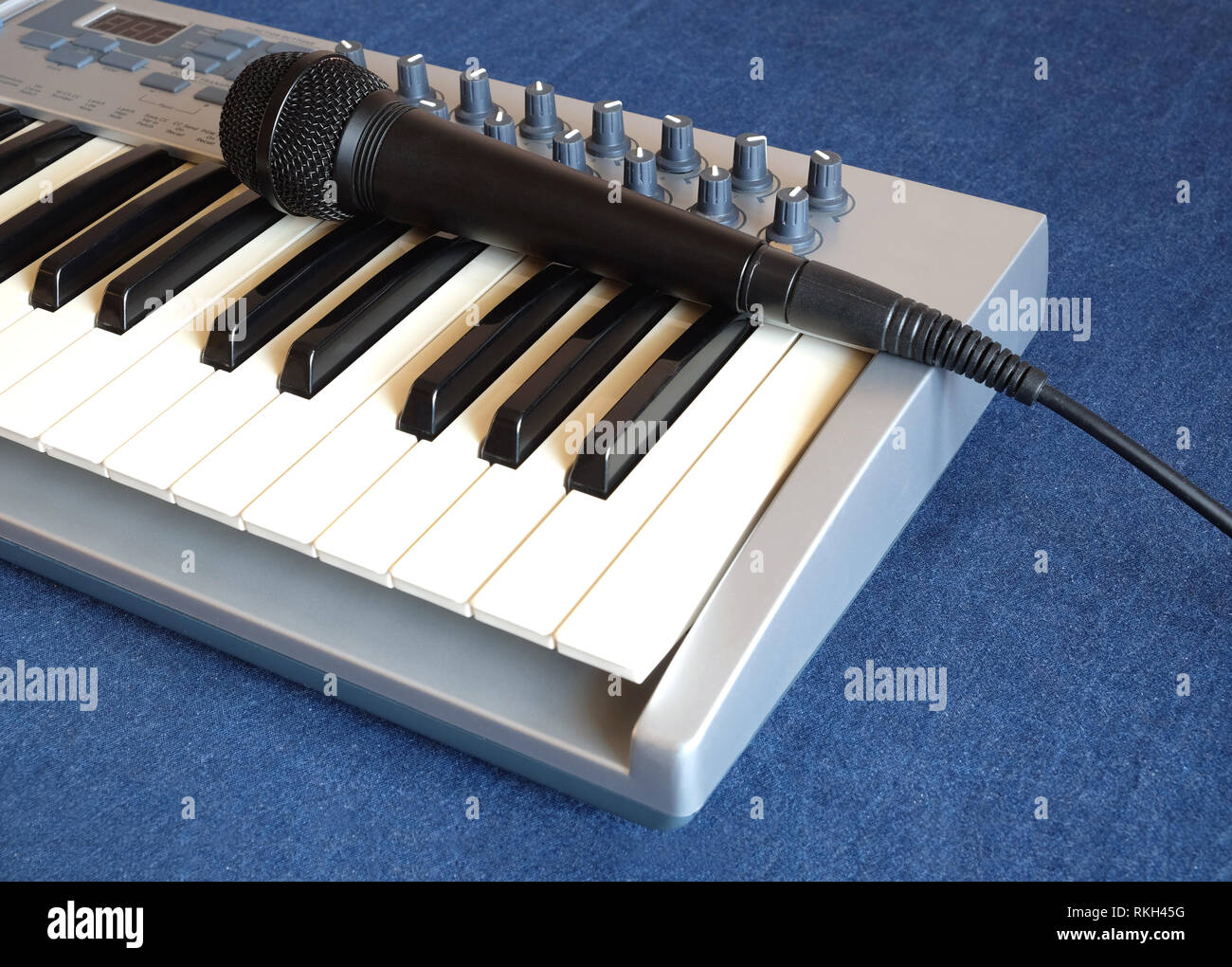 Black microphone on electronic synthesizer keyboard with many control knobs on denim background side view closeup - Stock Image