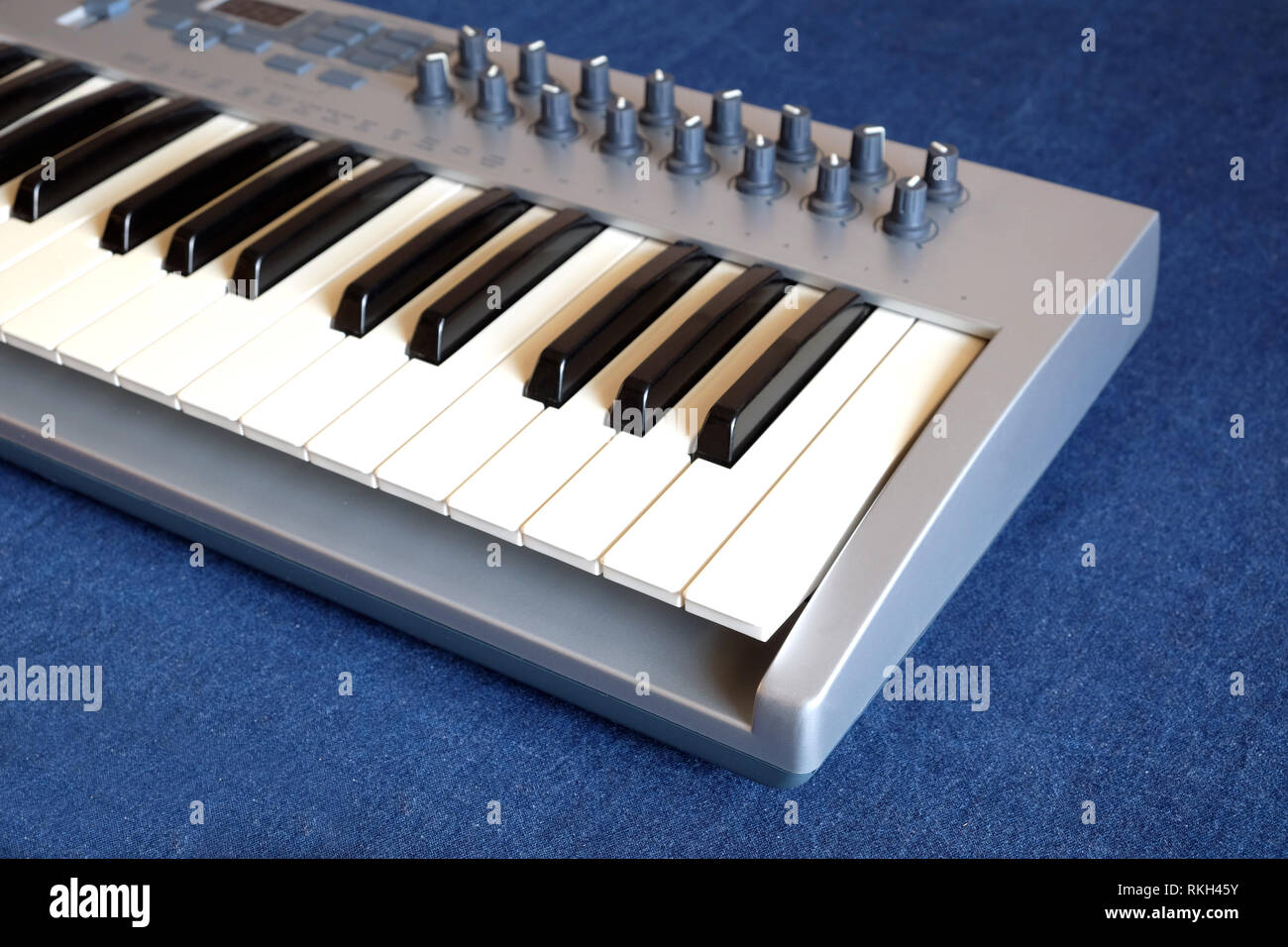 Electronic synthesizer keyboard with many control knobs on denim background side view closeup - Stock Image