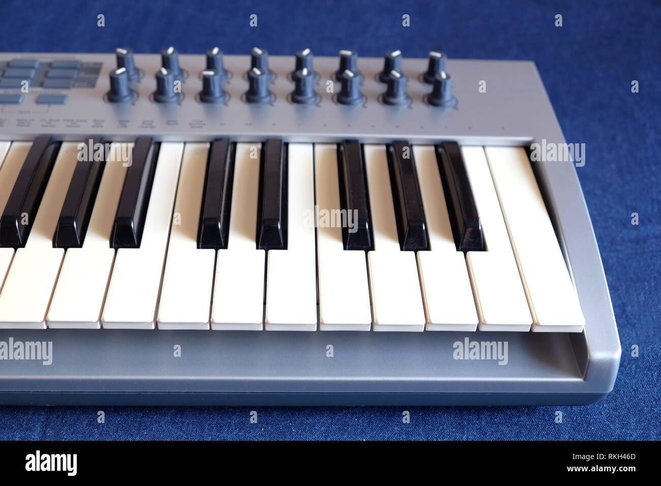 Electronic synthesizer keyboard with many control knobs on denim background top view closeup - Stock Image