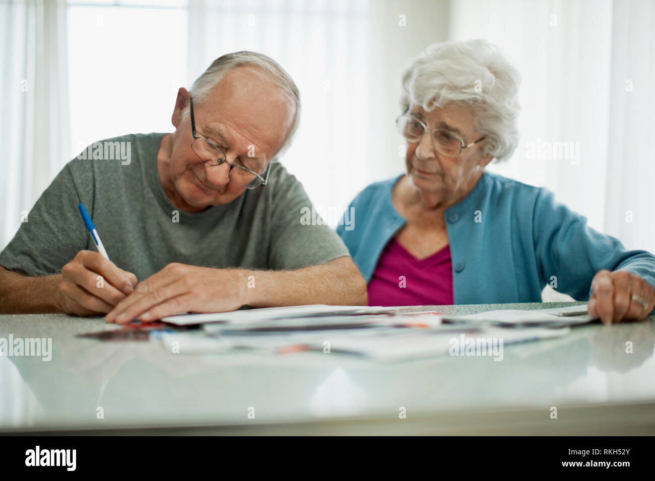 Anxious elderly couple sign some paperwork while they work through their big pile of bills. - Stock Image