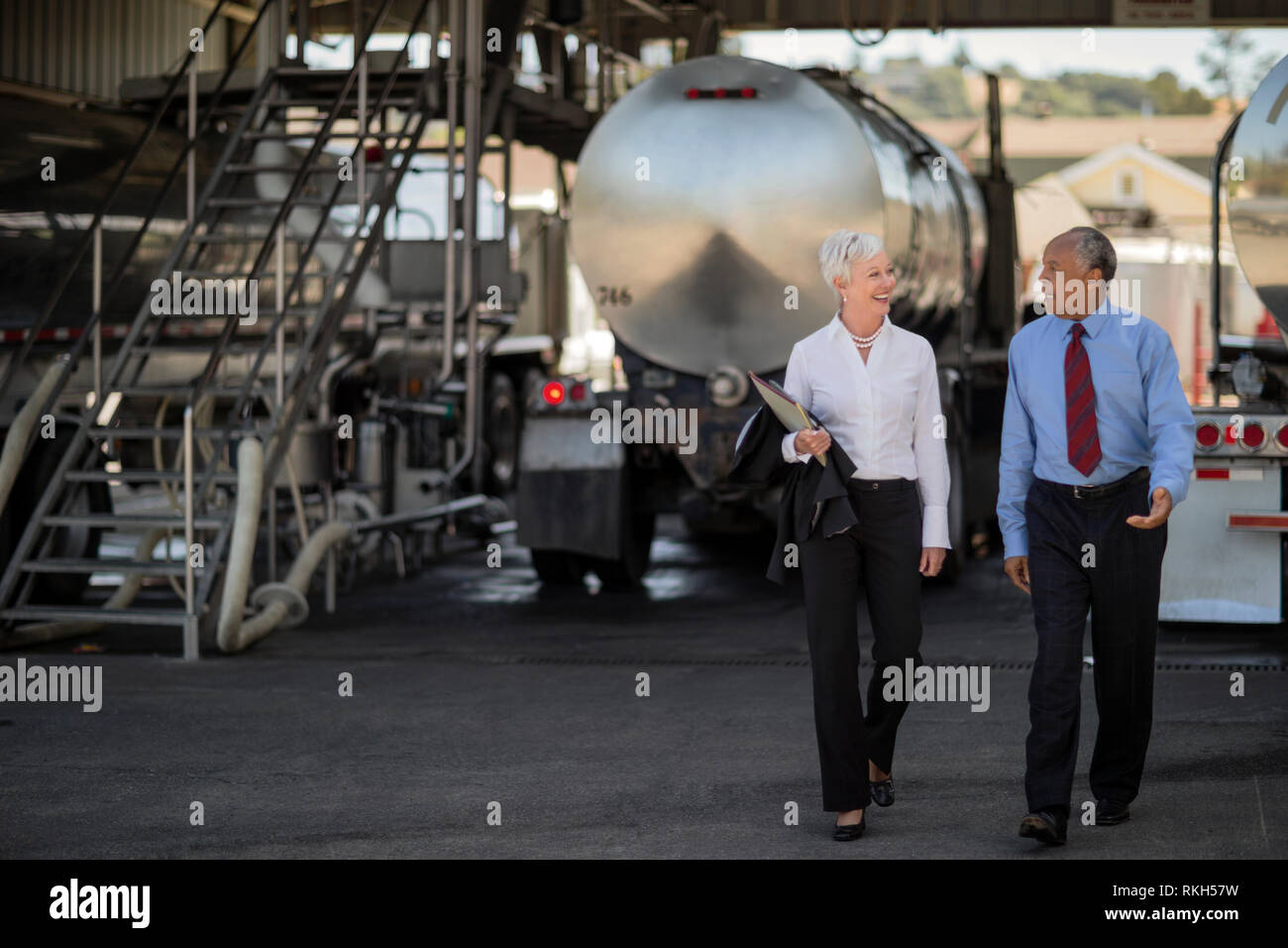 Two mature oil executives discuss the future direction of their company while at the oil truck yard. - Stock Image