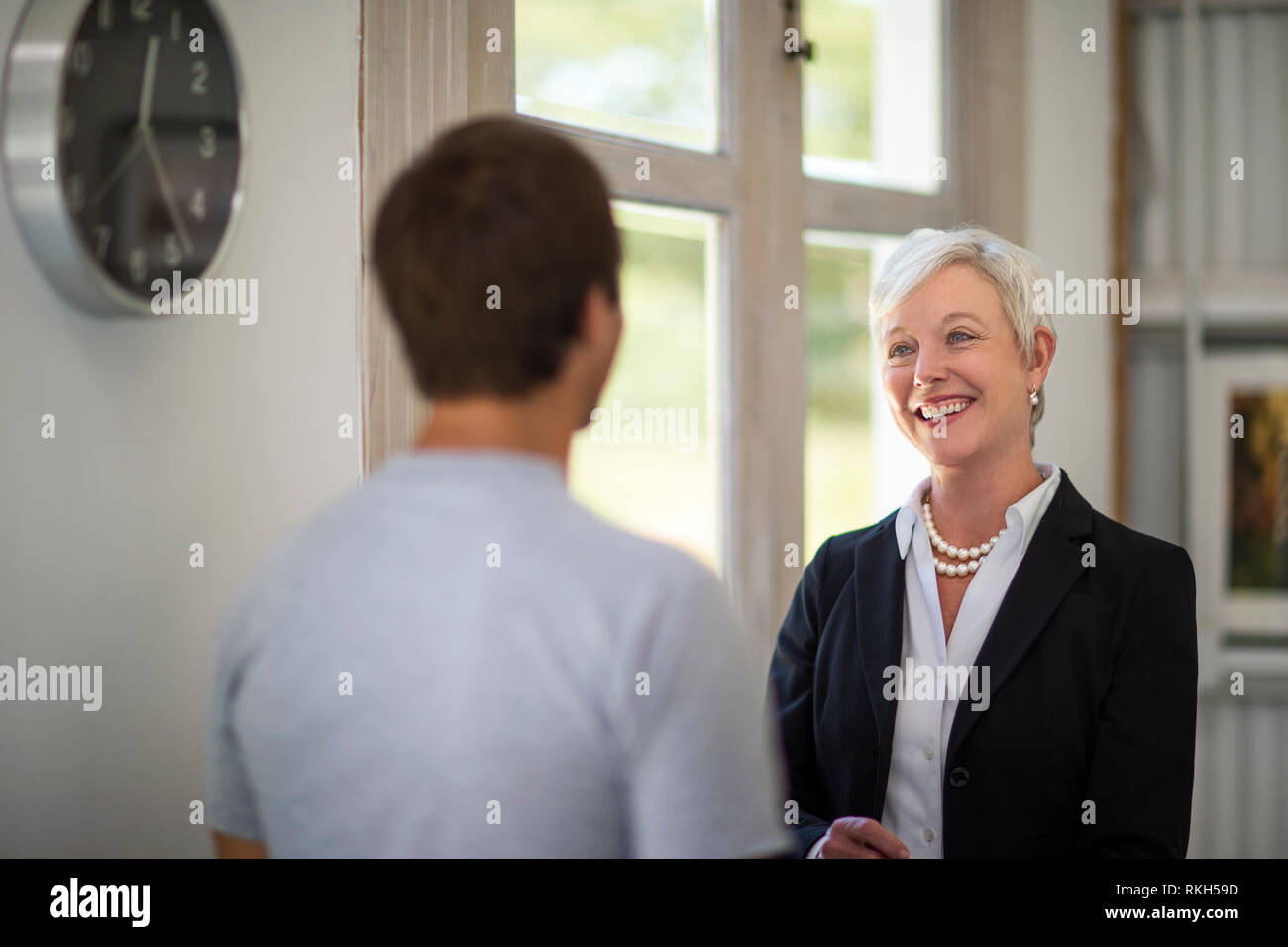 Smiling mature businesswoman chats to a young colleague. - Stock Image