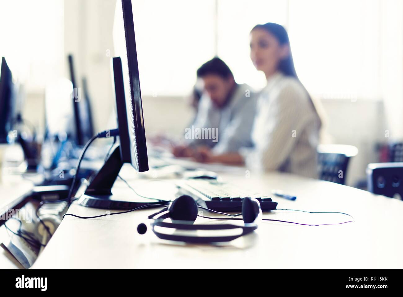 We are waiting for your call. Call center workers are working at modern office. Stock Photo