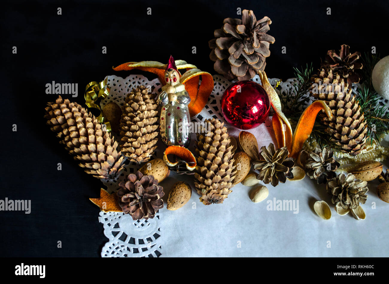 The edge of the paper napkin paper with various pine cones, pine twig, old worn Christmas decorations, almonds and orange peel on a black background - Stock Image
