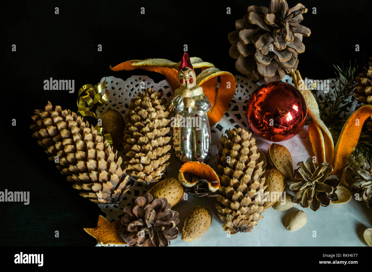 Paper napkin with with various pine cones, fir branch, old worn Christmas toys, almonds and orange peel on a black background Stock Photo