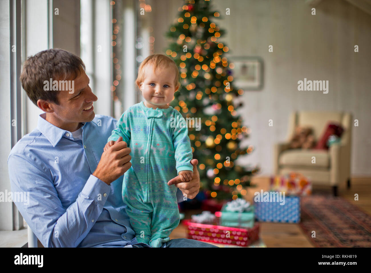 Portrait of a father holding his baby daughter at Christmas. - Stock Image