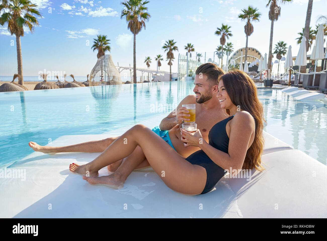 Young tourist couple on infinity pool hammock at resort on the beach drinking soda. - Stock Image