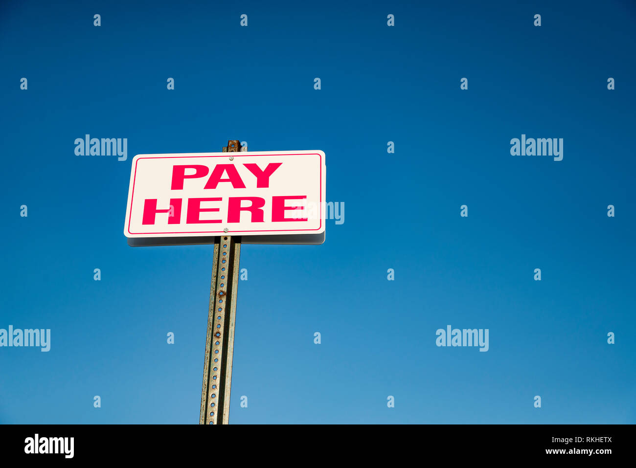 Pay Here signboard on top of an exterior wall with parked cars - Stock Image