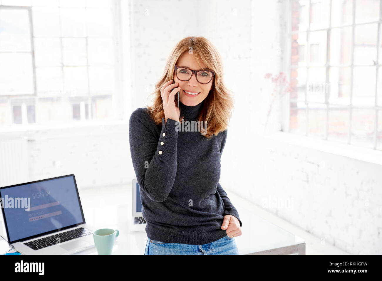 9c3b9836e85 Portrait of happy casual businesswoman using her mobile phone and making a  call while standing in