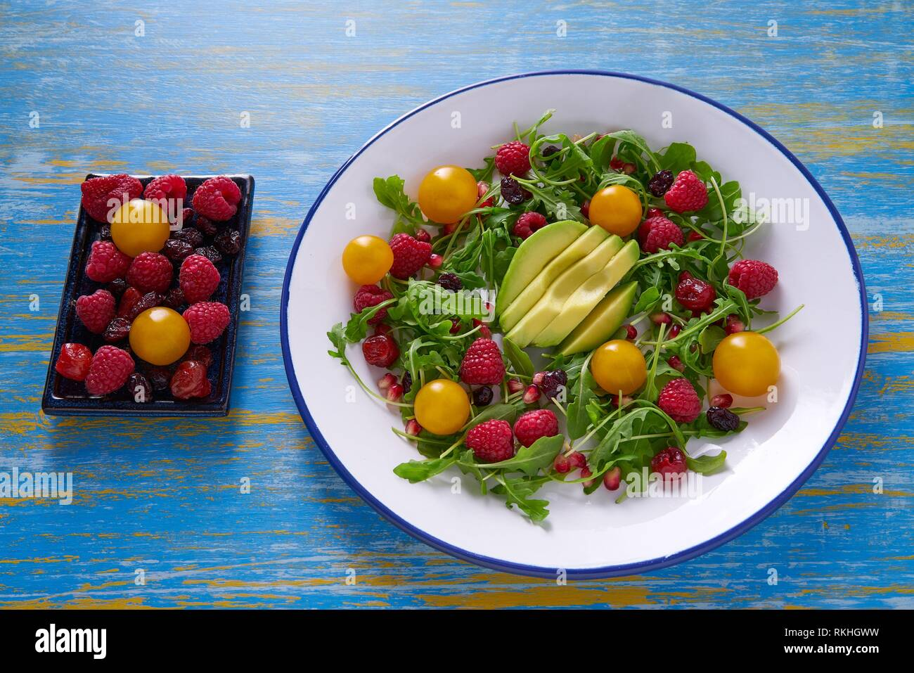 Avocado and berries salad with arugula and yellow cherry tomatoes. Stock Photo