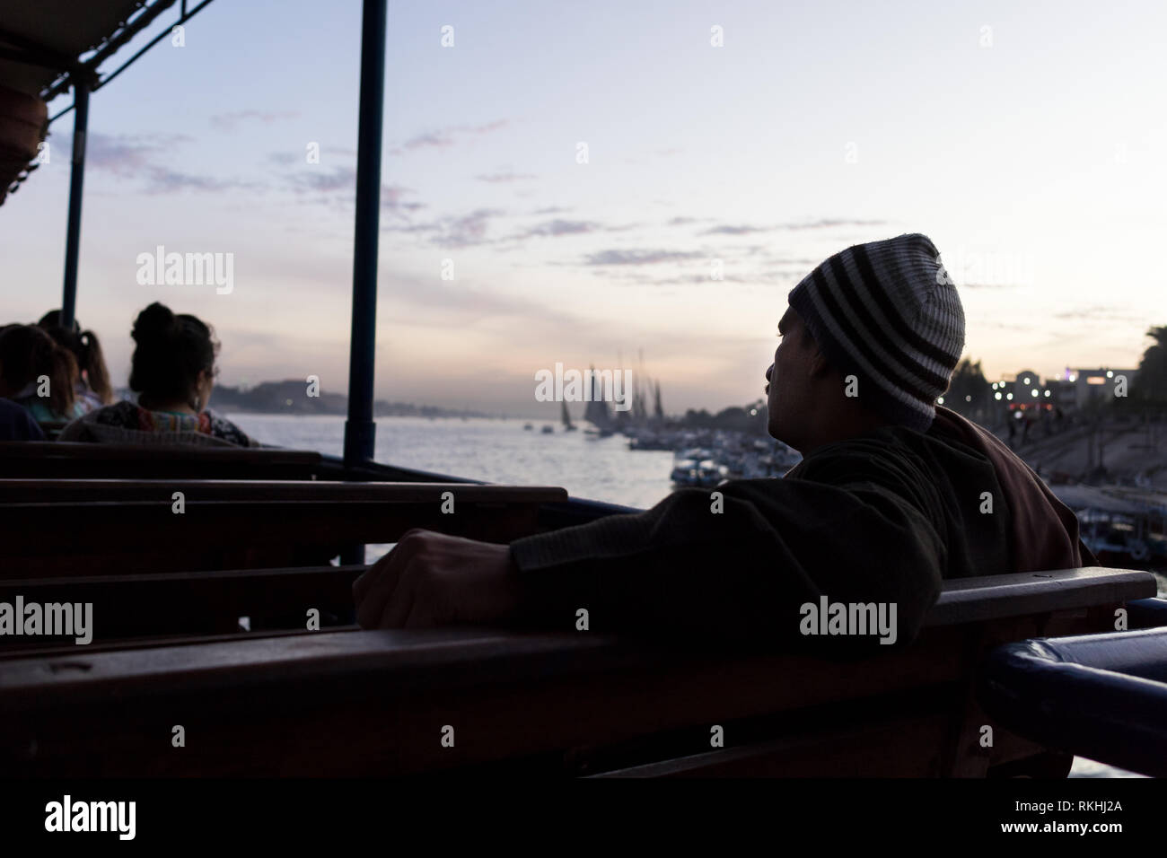 A man sits on the Luxor, Egypt, public ferry that crosses the Nile river - Stock Image