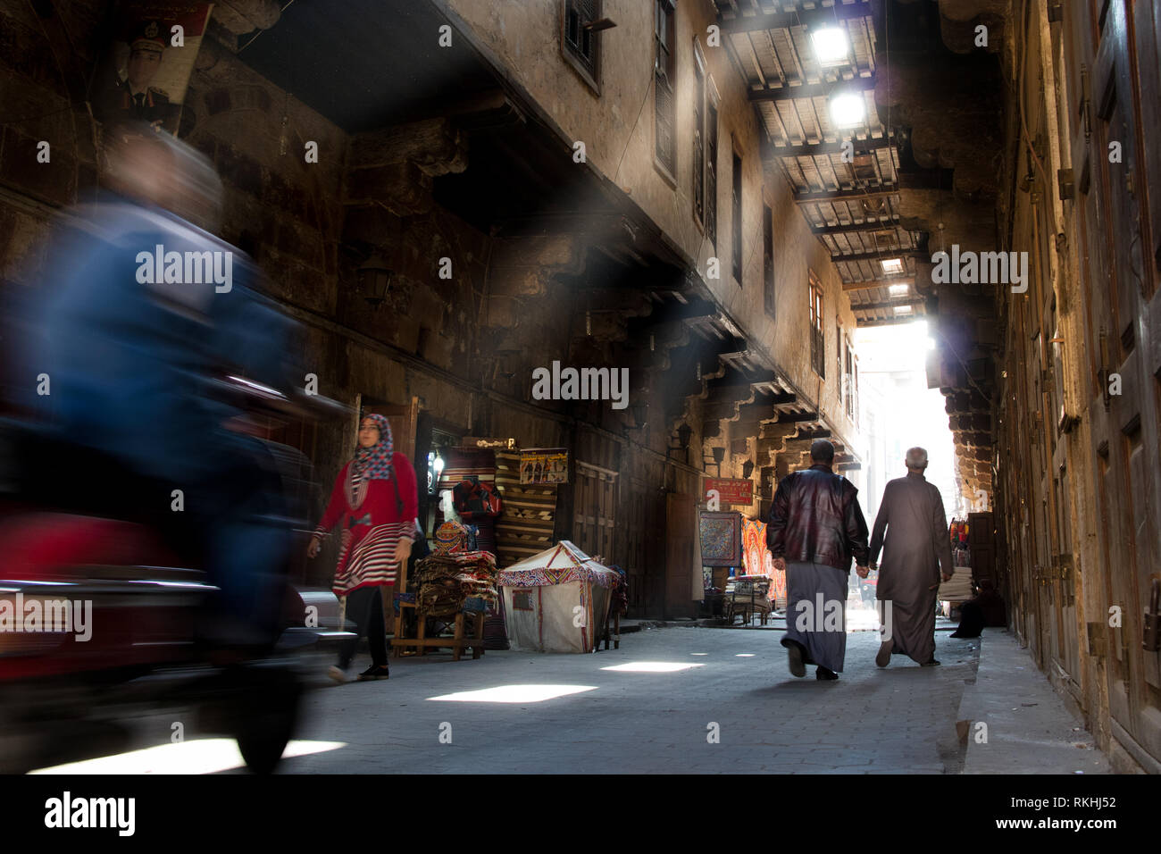 A busy covered street at Traditional Islamic Cairo in Egypt, wit people walking and a scooter passing at high speed - Stock Image