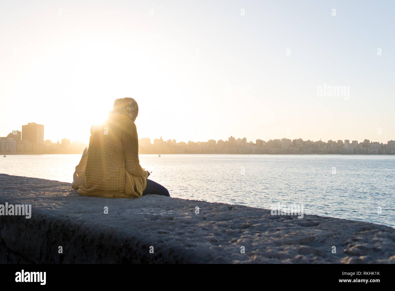 A woman sits looking at the phone next to the Mediterranean Sea at sunset time in Alexandria town, Egypt. - Stock Image