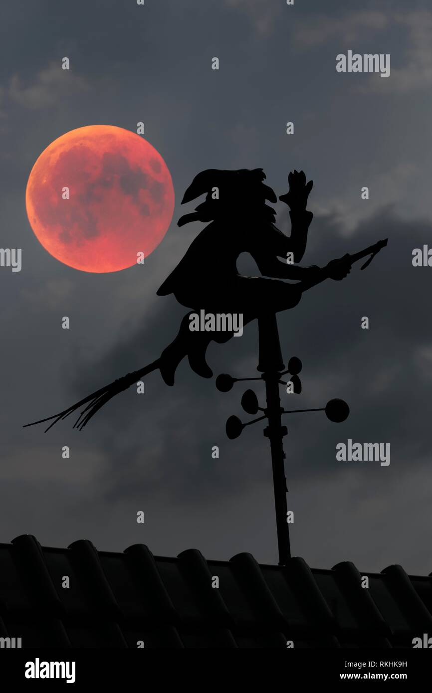 Blood moon over the roof of a house with weather vane with weather witch, Baden-Württemberg, Germany - Stock Image