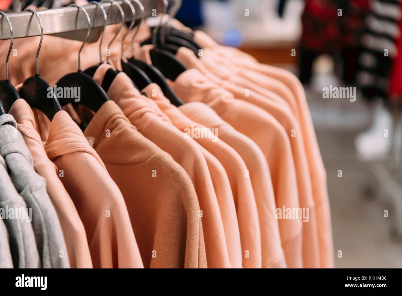 Many One-colour Hooded Sweatshirt On Hanger In Store Of Shopping Center. - Stock Image