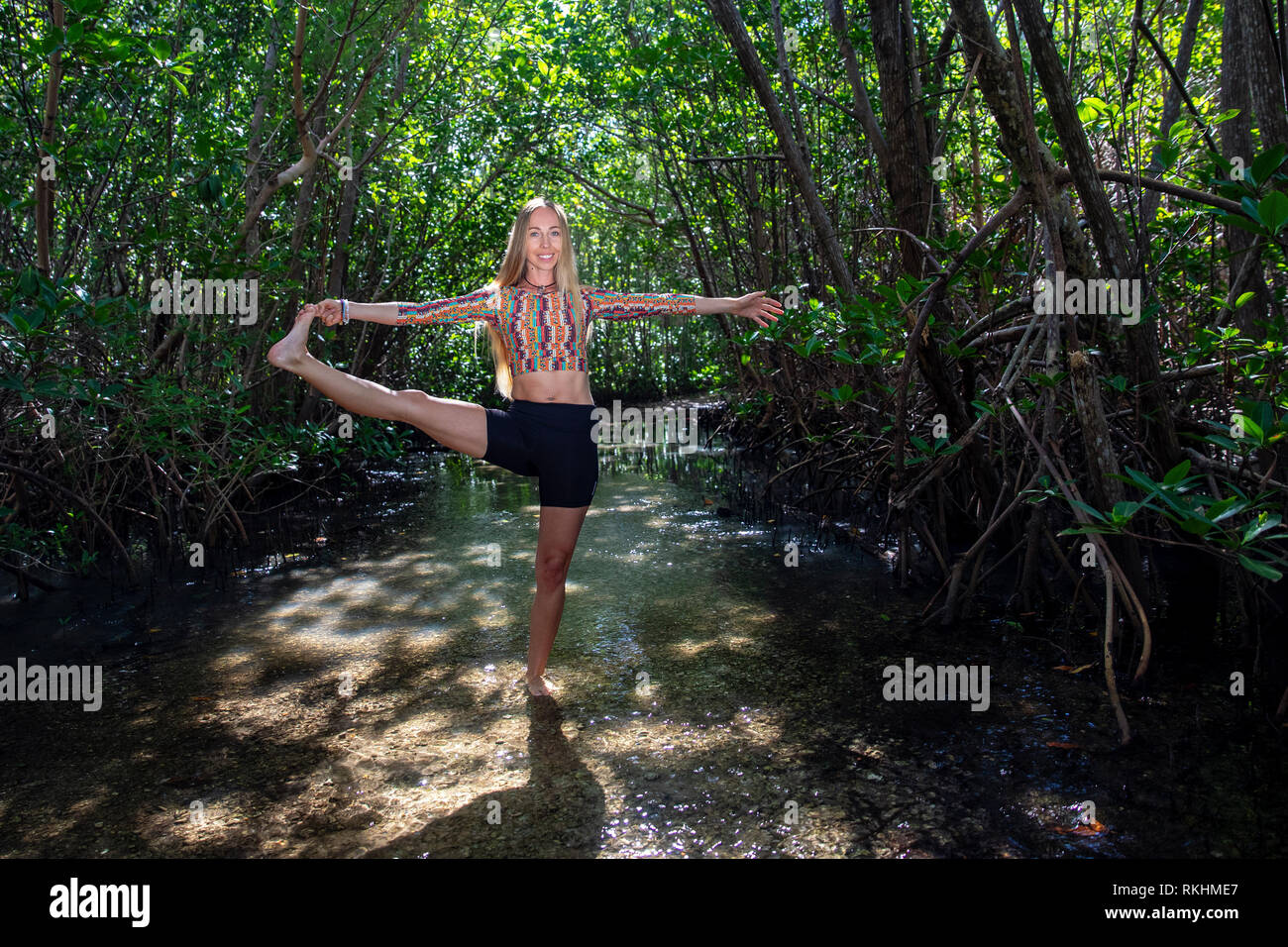 Young woman practicing yoga (Extended Hand-to-Big-Toe Pose - Utthita Hasta Padangustasana) in a natural setting - Fort Lauderdale, Florida, USA - Stock Image