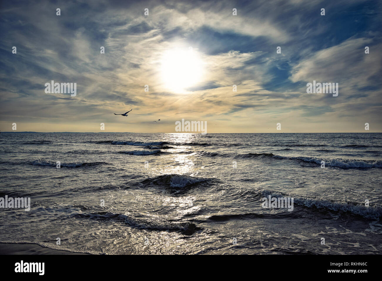 Sunset and a picturesquely dramatic cloudy sky over the stormy sea - Stock Image
