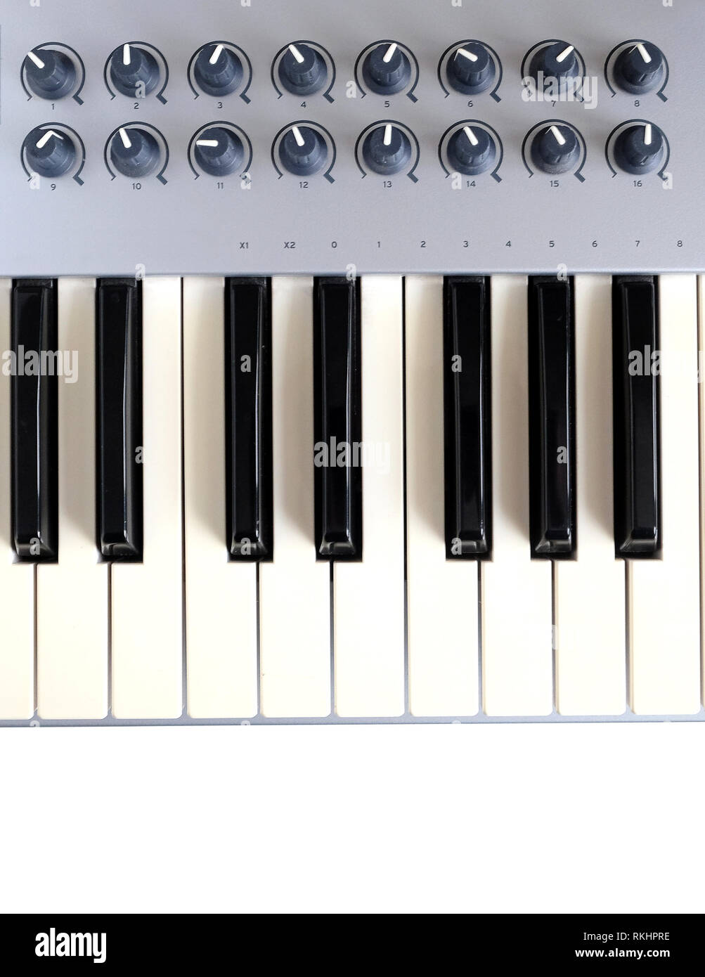 Fragment of electronic synthesizer keyboard with many control buttons isolated on white background top view closeup - Stock Image
