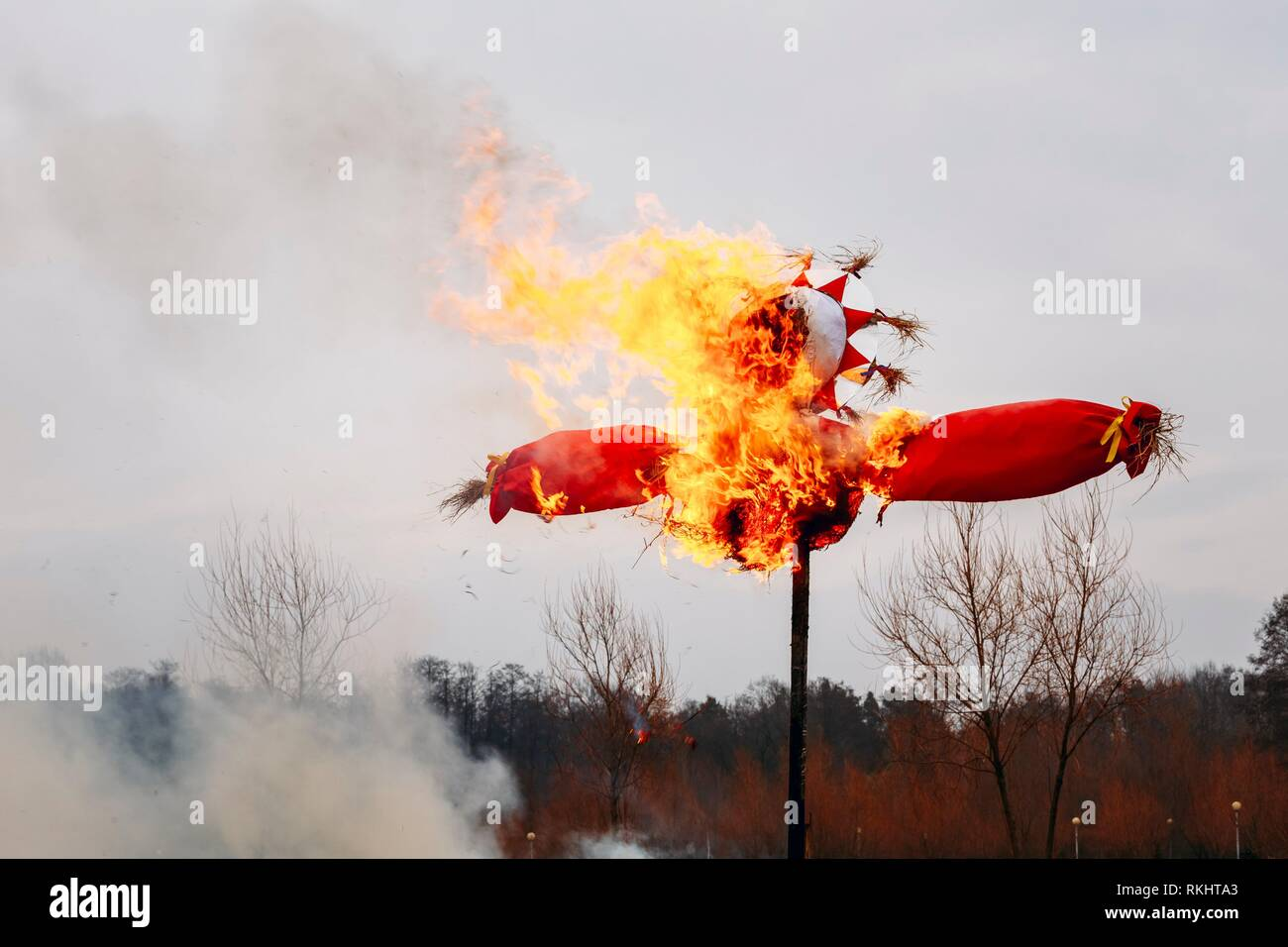 Burning effigies straw Maslenitsa in fire on the traditional holiday dedicated to the approach of spring - Slavic celebration Shrovetide. - Stock Image