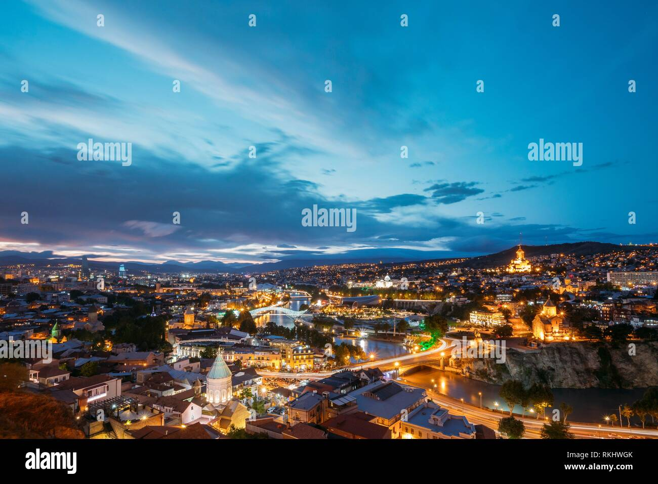 Scenic Top View Of Tbilisi, Georgia In Bright Evening Illumination With All Famous Landmarks, Sightseeings. Dramatic Blue Cloudy Sky Background. Stock Photo