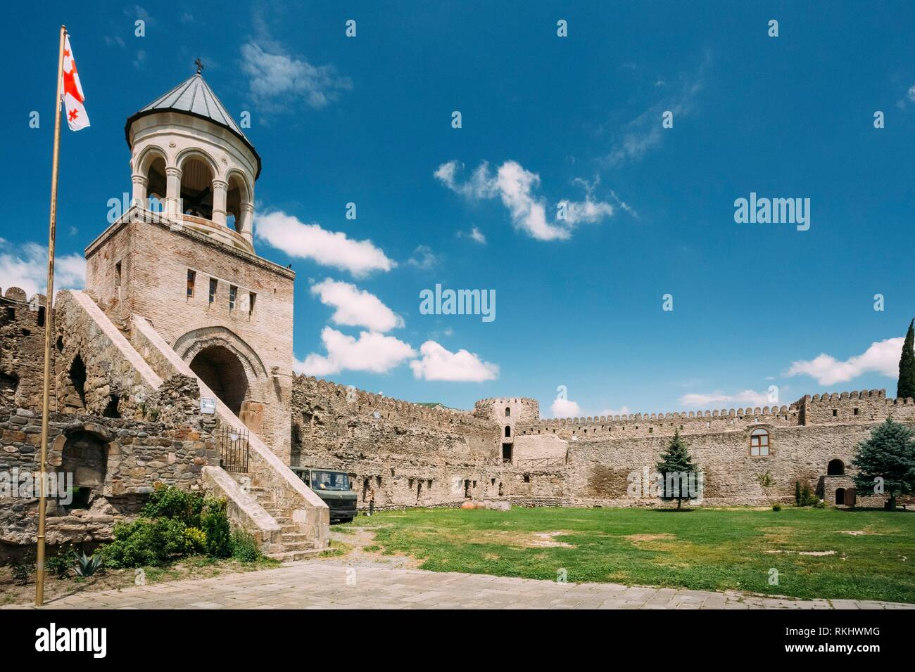 Mtskheta, Georgia. The View Of Inner Courtyard With A Tower Of Svetitskhoveli Cathedral Of The Living Pillar Surrounded By Gray Stone Fortified Wall - Stock Image